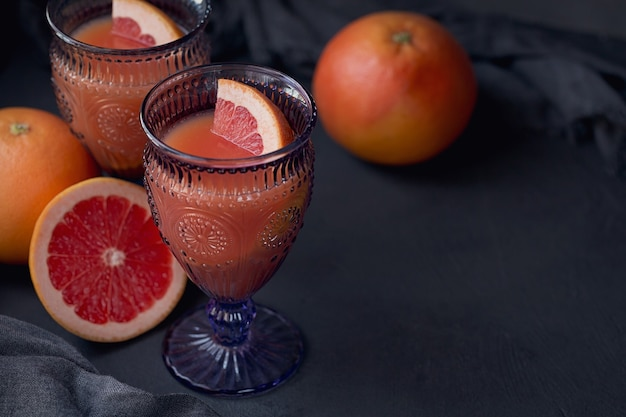 Glas vers geperst grapefruitsap met verse citrusvruchten
