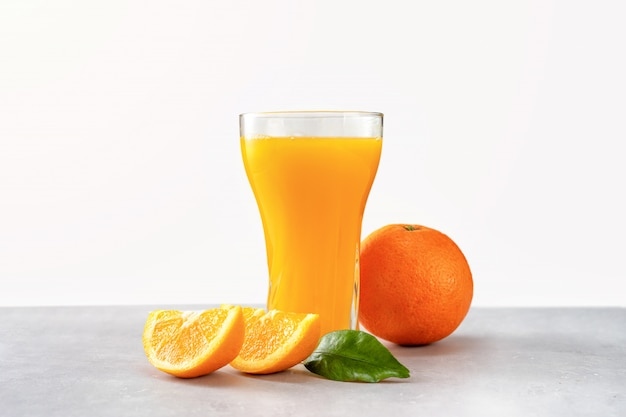 Glas vers jus d'orange met sinaasappelen dat op wit wordt geïsoleerd