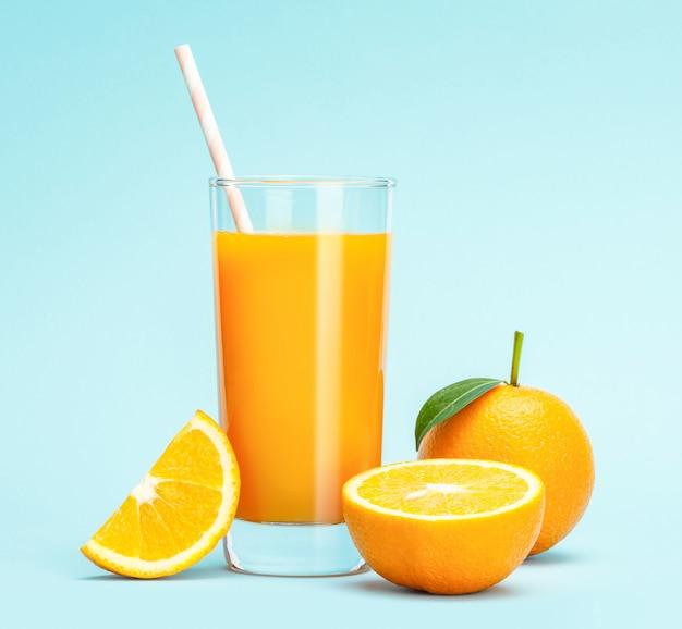 Glas vers jus d'orange op houten tafel, vers fruit jus d'orange in glas met een groep sinaasappel op blauwe muur, selectieve aandacht op glas