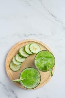 Glas vers komkommersap op marmeren achtergrond