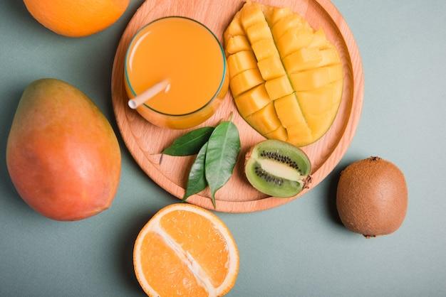 Glas vers sinaasappel- en mangosap en plakje oranje fruit op donkere achtergrond