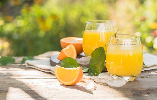 Glas vers sinaasappelsap, rijp sinaasappelfruit en plakjes op natuurlijk. vers geperst sinaasappelsap met rietje, sinaasappelfruit en sinaasappelplakken.