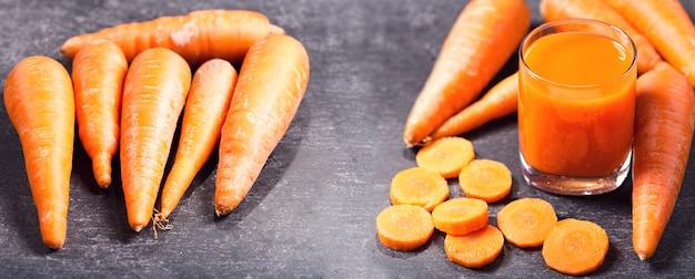 Glas vers wortelsap met groenten op donker