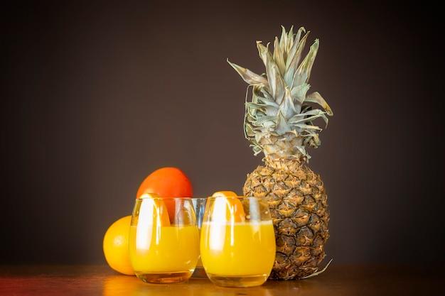 Glas verse ananas en sinaasappel smoothie op houten tafel geïsoleerd b