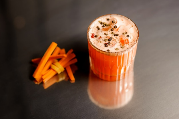 Glas verse en gezonde wortelcocktail die met peper wordt verfraaid