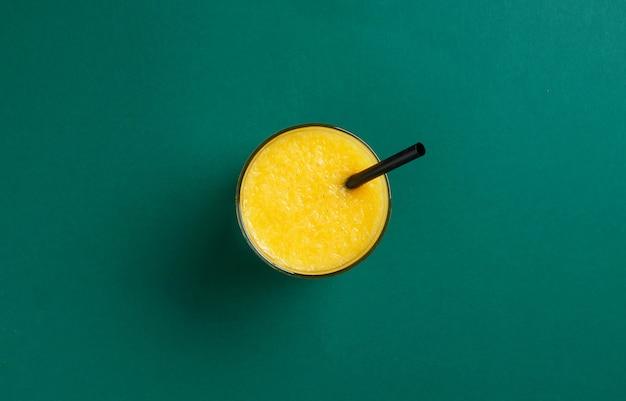Glas verse jus d'orange met zwart stro op groene achtergrond, bovenaanzicht