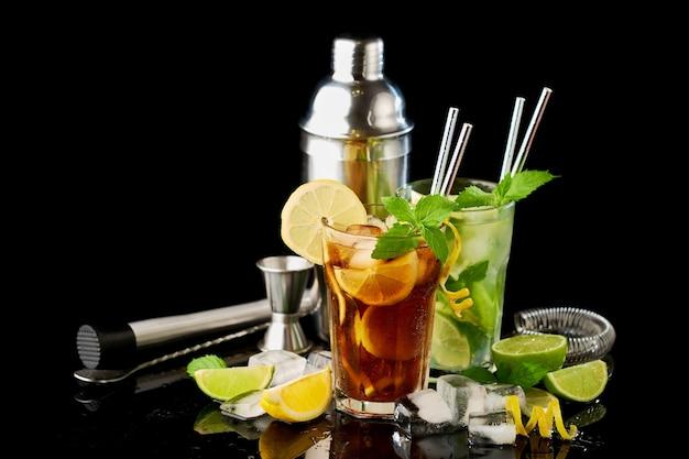 Glas verse long island ice tea en mojito cocktail studio opname op zwarte achtergrond