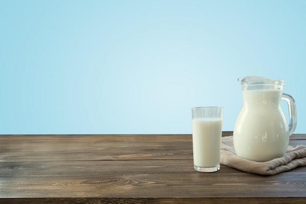 Glas verse melk en kruik op houten tafelblad met blauwe muur als achtergrond.