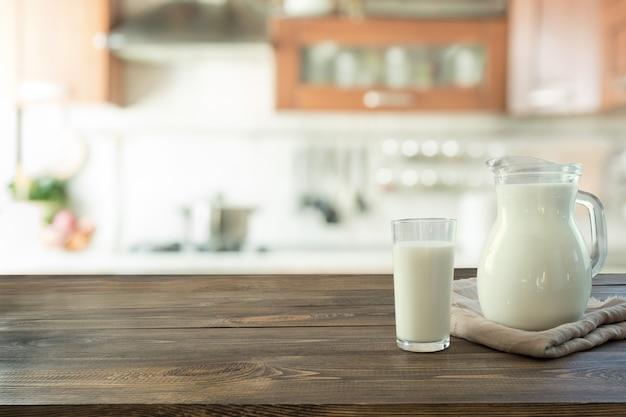 Glas verse melk en kruik op houten tafelblad met onduidelijk beeldkeuken als achtergrond.