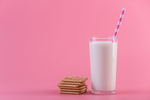 Glas verse melk met een rietje en koekjes op een roze achtergrond. kleurrijk minimalisme. gezonde zuivelproducten
