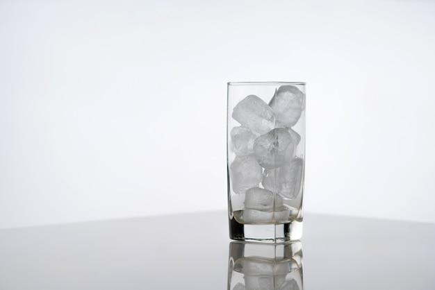 Glas vol met ijs op wit oppervlak.