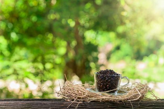 Glas vol met koffiebonen op hooi