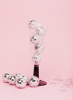 Glas voor champagne gevuld met zilveren kerstballen