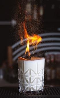Glas vurige cocktail op de donkere toog