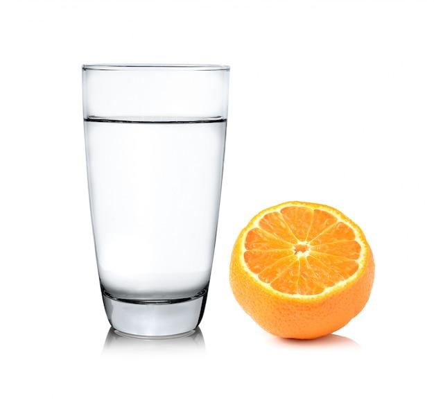 Glas water en half oranje fruit op witte ruimte, vers en sappig