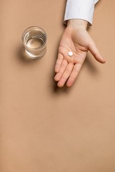 Glas water en medicijnen in de hand