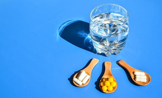 Glas water en pillen op houten lepel op blauwe achtergrond met hard licht en schaduwen. creatief. vitaminen en prebiotica, probiotica. herfst vitamine dosis.