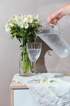 Glas water en vaas met bloemen