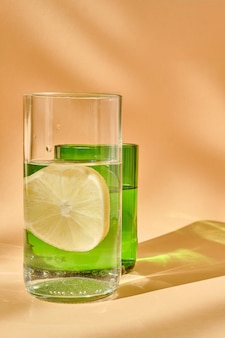 Glas water met citroen en een groen glas. lichtspel