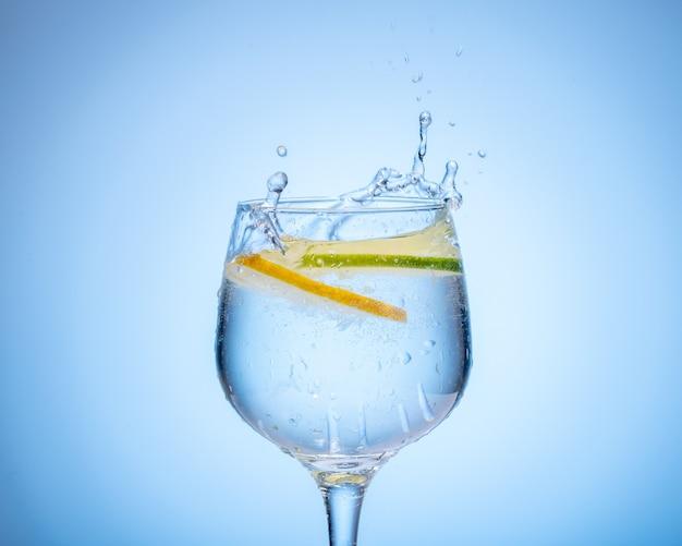 Glas water met citroen viel in en plons op lichtblauwe gradiëntachtergrond.