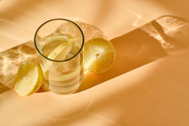 Glas water met citroen. vlakbij ligt een in plakjes gesneden citroen.