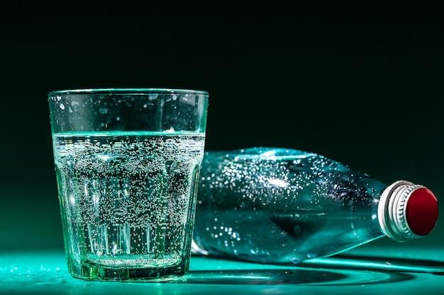 Glas water met een fles op tafel