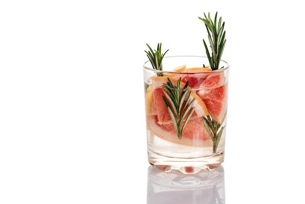 Glas water met grapefruit en rozemarijn op een witte achtergrond.
