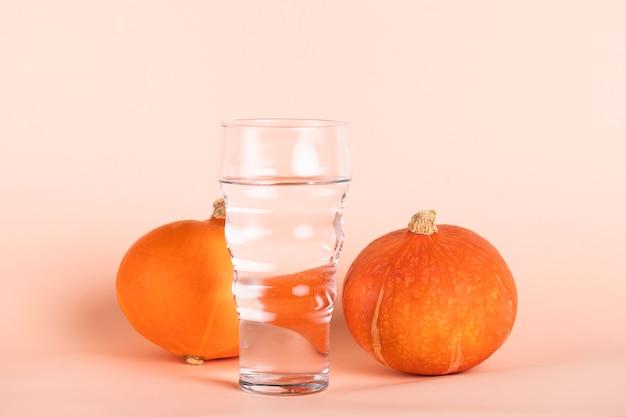 Glas water met kleine pompoenen