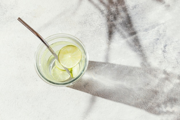 Glas water met schijfjes citroen op tafel
