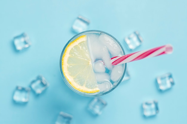 Glas water of drankje met ijs en citroen op een blauwe ondergrond met ijsblokjes. concept van een hete zomer, alcohol, koel drankje, dorst lessen. plat lag, bovenaanzicht