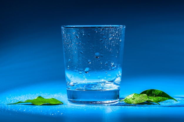 Glas water op een tafel in het donker
