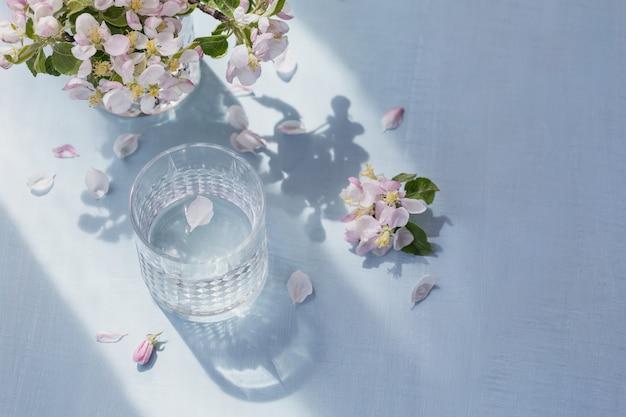 Glas water op tafel met bloeiende appelboomtak in een glas
