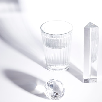 Glas water; prisma; fonkelende diamant op witte achtergrond