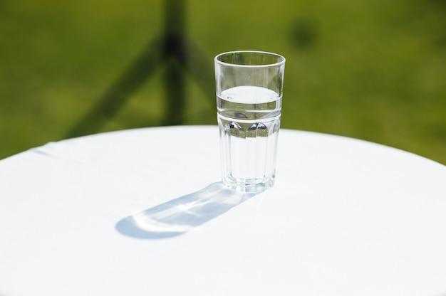 Glas water verlicht met zon op een witte tafel