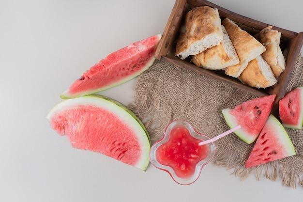 Glas watermeloen smoothie en mandje brood op witte tafel.