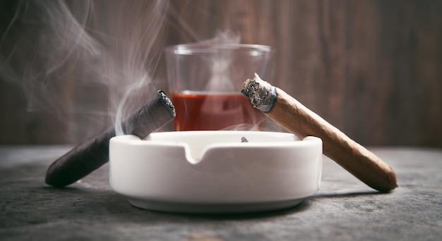 Glas whisky, asbak en sigaren op tafel
