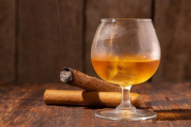 Glas whisky en aangestoken sigaar in een asbak op houten