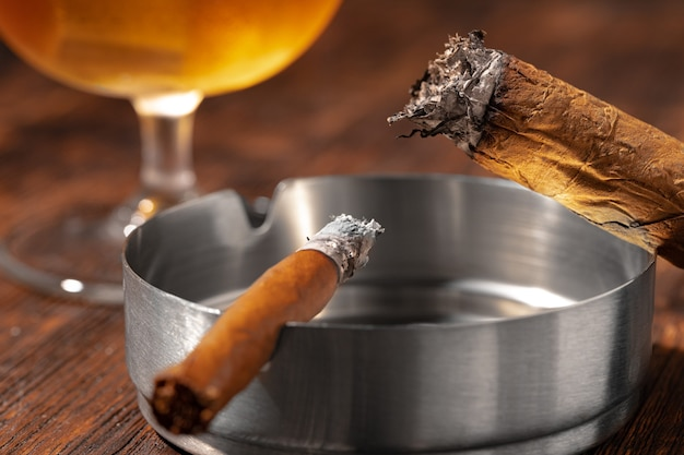 Glas whisky en aangestoken sigaar in een asbak