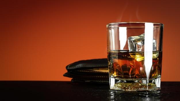 Glas whisky en ijsblokje op rood