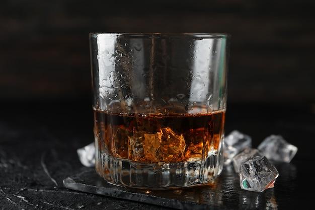 Glas whisky en ijsblokjes op zwart