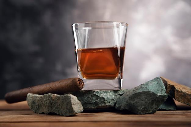 Glas whisky en sigaar op steen
