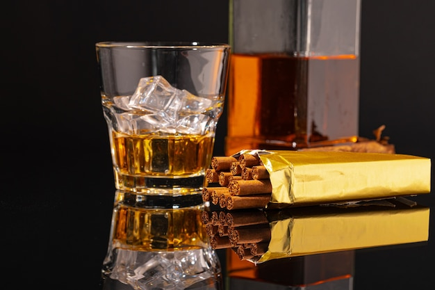 Glas whisky en sigaar op zwarte achtergrond