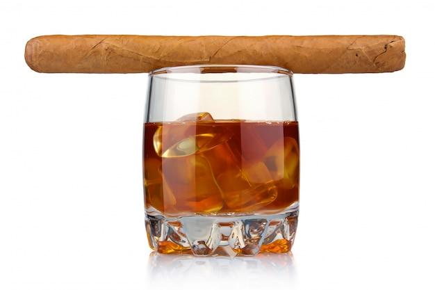 Glas whisky met geïsoleerde ijsblokjes en de havana sigaar