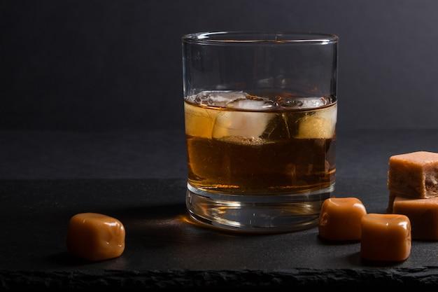 Glas whisky met ijs en karamelsuikergoed op een zwarte leisteenraad op zwarte achtergrond. zijaanzicht, low key.