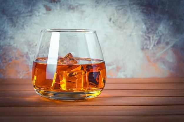 Glas whisky met ijs. stilleven. brandy, bourbon op een bruin houten tafel. sterke alcoholische drank. rum, whisky. ruimte voor tekst kopiëren.