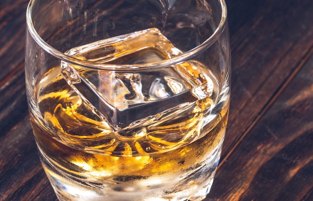 Glas whisky met ijsblokje op houten tafel