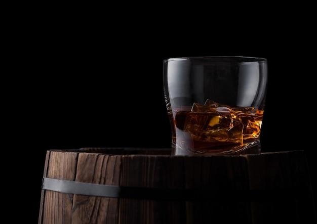 Glas whisky met ijsblokjes bovenop houten vat