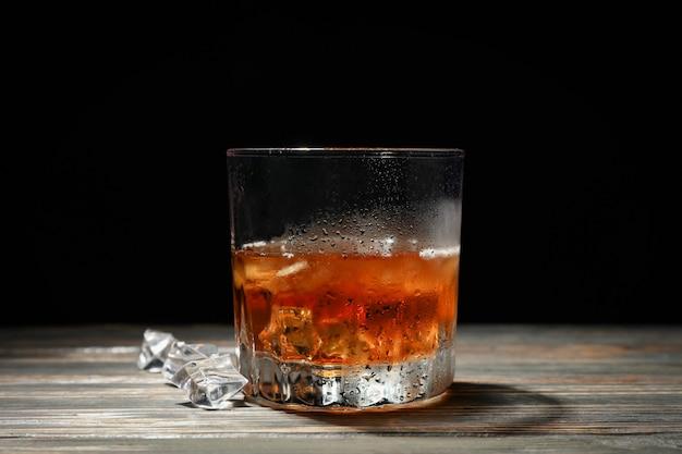 Glas whisky met ijsblokjes op houten achtergrond, ruimte voor tekst