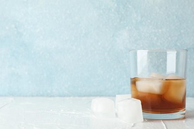 Glas whisky met ijsblokjes op witte achtergrond, ruimte voor tekst