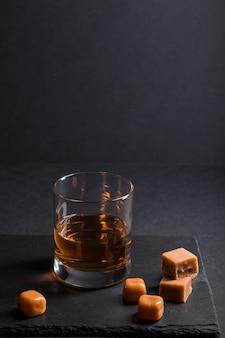 Glas whisky met karamelsuikergoed op een zwarte leisteenraad op zwarte achtergrond. zijaanzicht, low key, kopieer ruimte.
